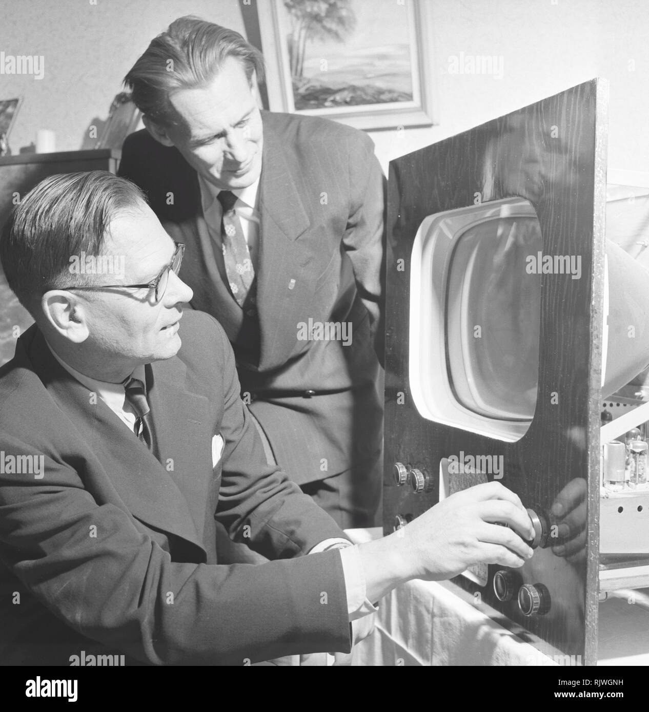 Television in the 1950s. A man with an early television set in production or testing is adjusting the picture. November 1953 Stock Photo