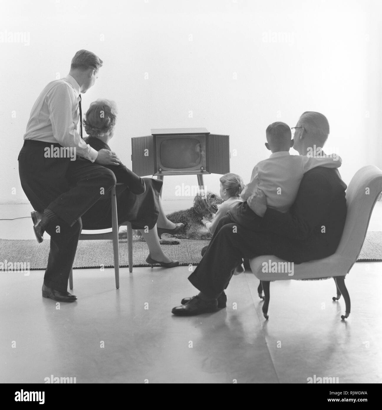 Television in the 1950s. Family in front of a television set and fascinated by the new television medium in March 1959. Sweden - Stock Image