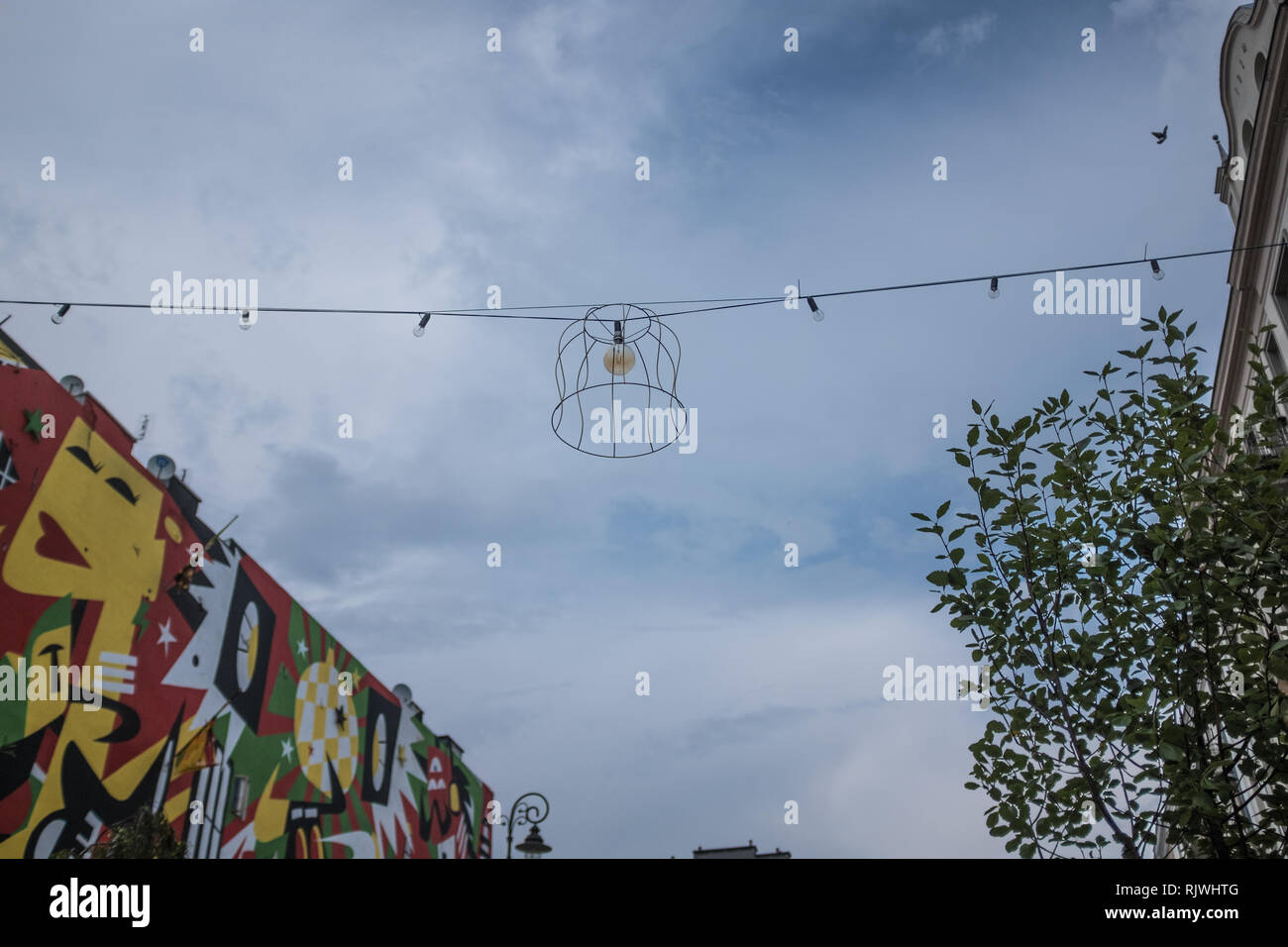festive lighting across a street with a graffiti wall Stock Photo