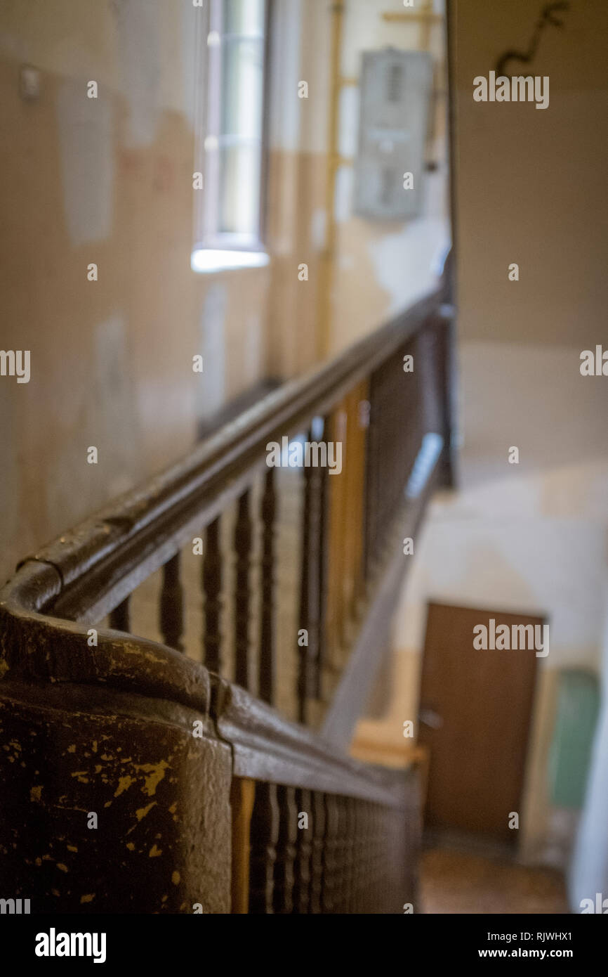 bannister curving round on a staircase leading down to a door Stock Photo