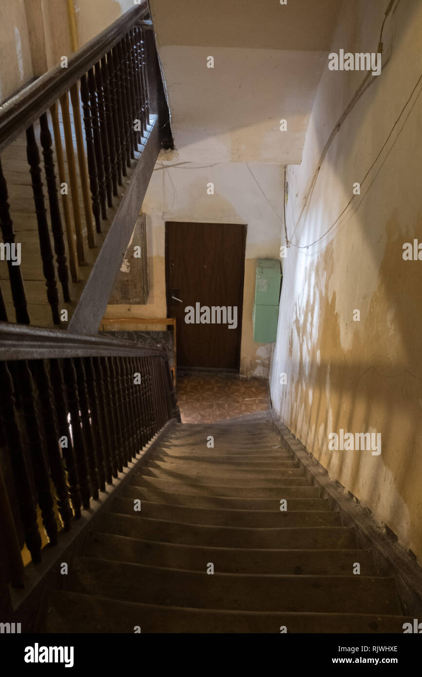 empty staircase in shadow leading down to a door in a tenement house in Warsaw Stock Photo