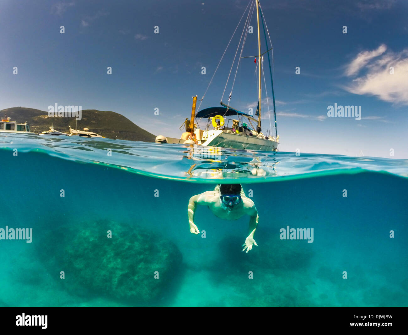 Split level photo of a Man swimming in clear blue sea with a yacht in the background half the shot above water and half in the sea using a Dome camera - Stock Image