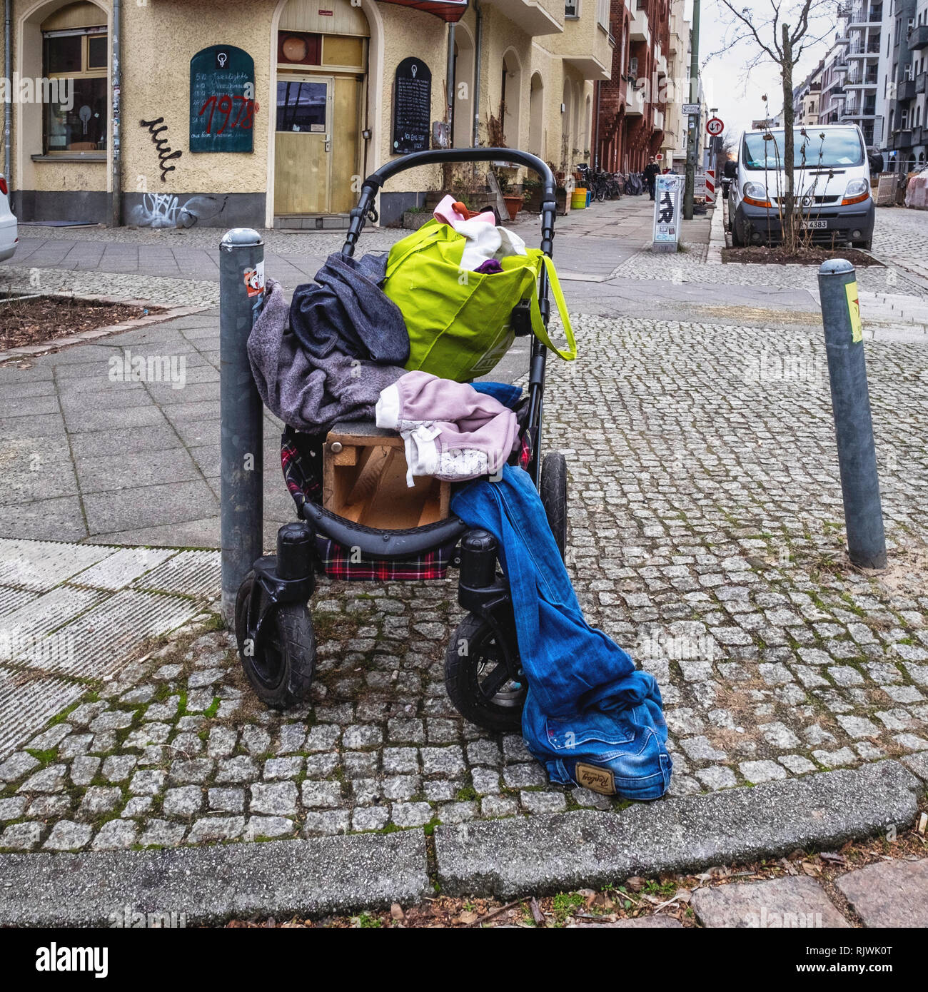Berlin, Friedrichshain. Child's pram and old second-hand used clothing dumped on pavement. No longer needed & abandoned clothes - Stock Image
