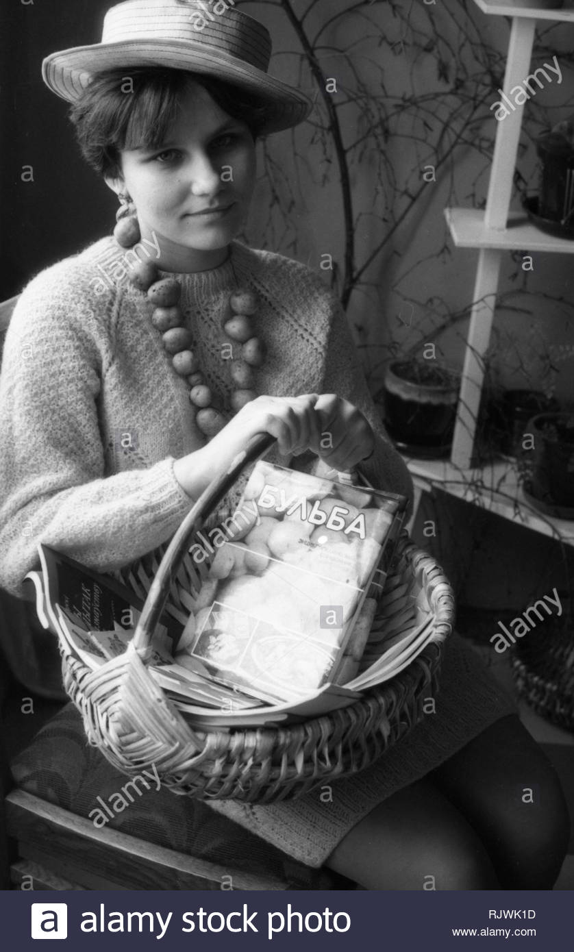 The portrait of charming Belorussian lady. The lady is sitting in  room on the chair. She's wearing a straw hat. On her neck are put the beads from real young potatoes. Look of the lady is thoughtful. The wicker rod basket stands on her knees. The recipe book and magazenes are inside of basket. The book describes 500 recipes for cooking potatoes. After all potatoes are considered the first product in our country.  There houseplants in pots are around the elegant lady in room. - Stock Image