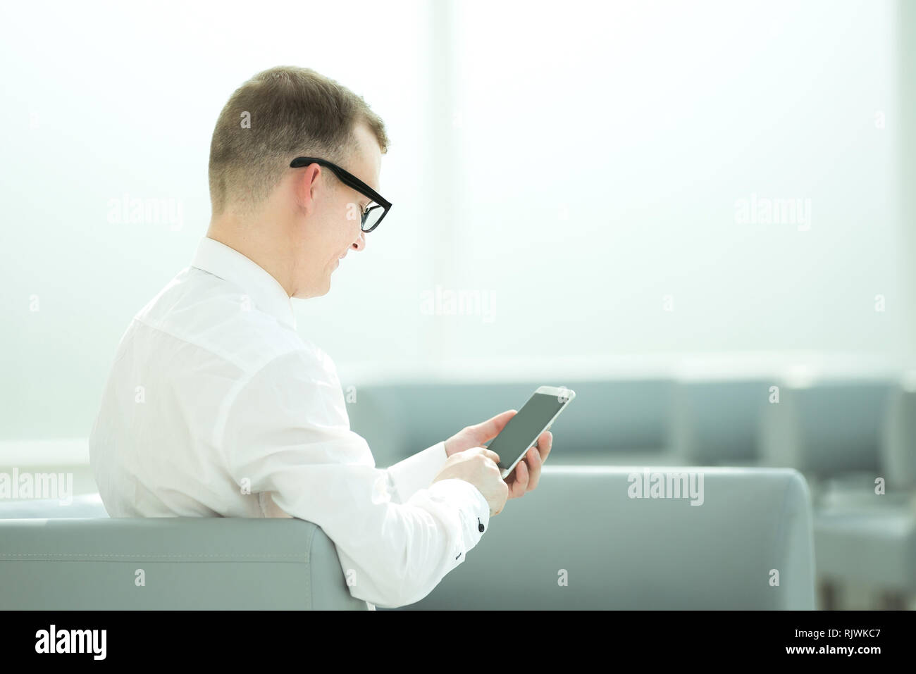 young businessman typing SMS on his smartphone. Stock Photo