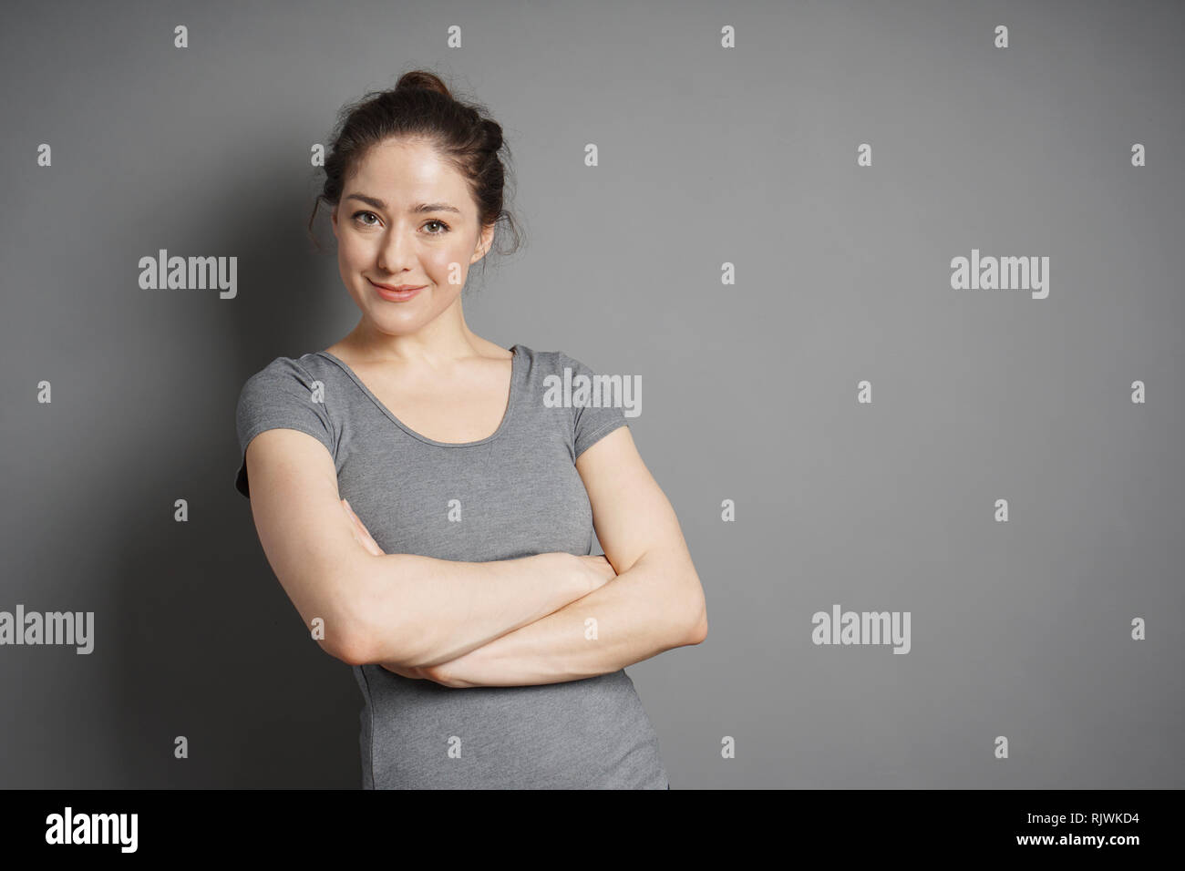 young woman with contented smile and crossed arms against gray background with copy space - Stock Image