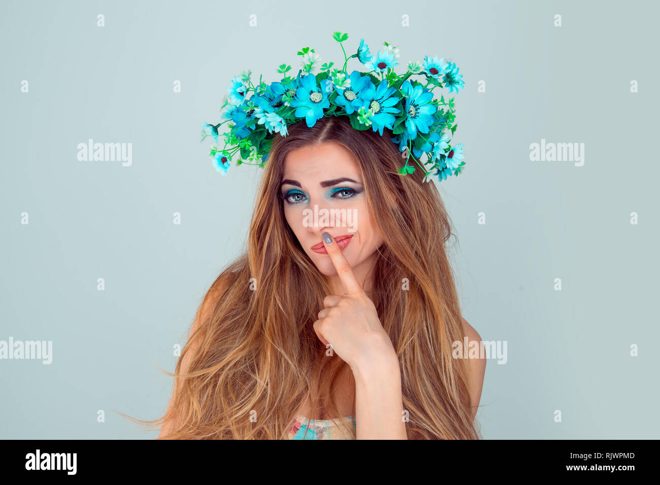 Upset skeptical woman with anemone floral headband looking at you camera frustrated finger on lips thoughtful isolated on blue background. Fashion bea - Stock Image