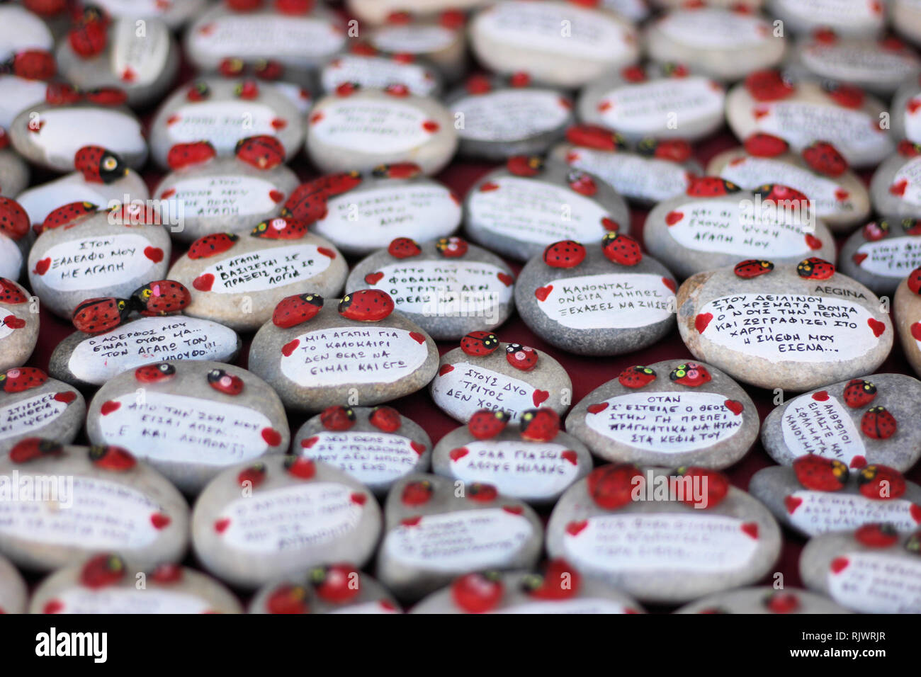 Round pebbles message stones, handmade souvenirs on Greek island - Stock Image