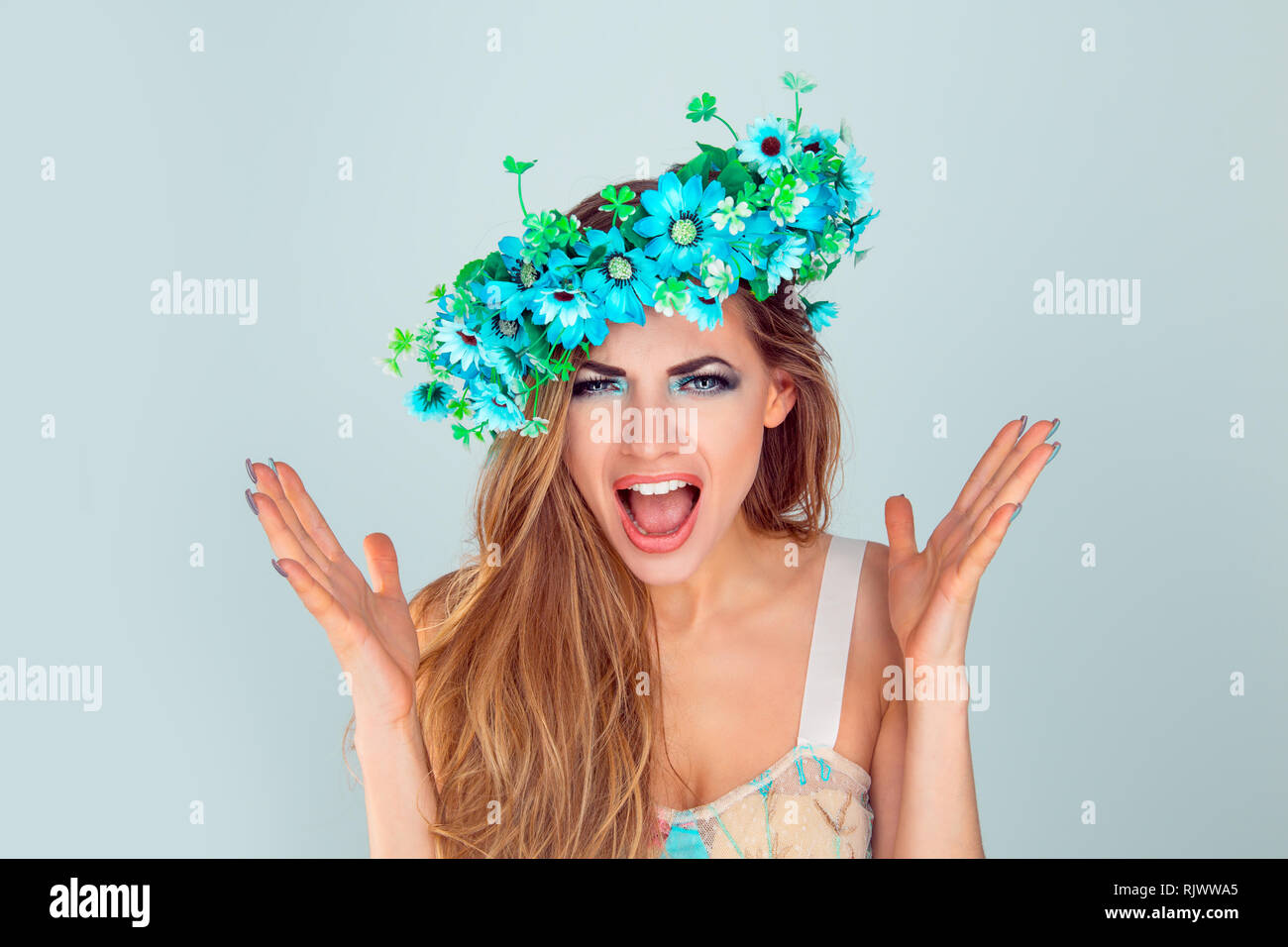 Angry woman with headband from flowers screaming in horror - Stock Image