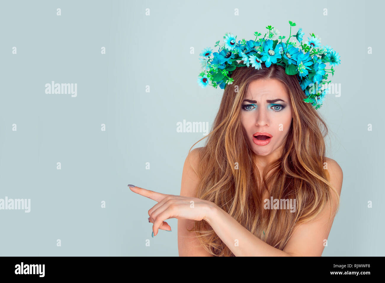Stunned woman with floral headband pointing with index finger to copyspace - Stock Image