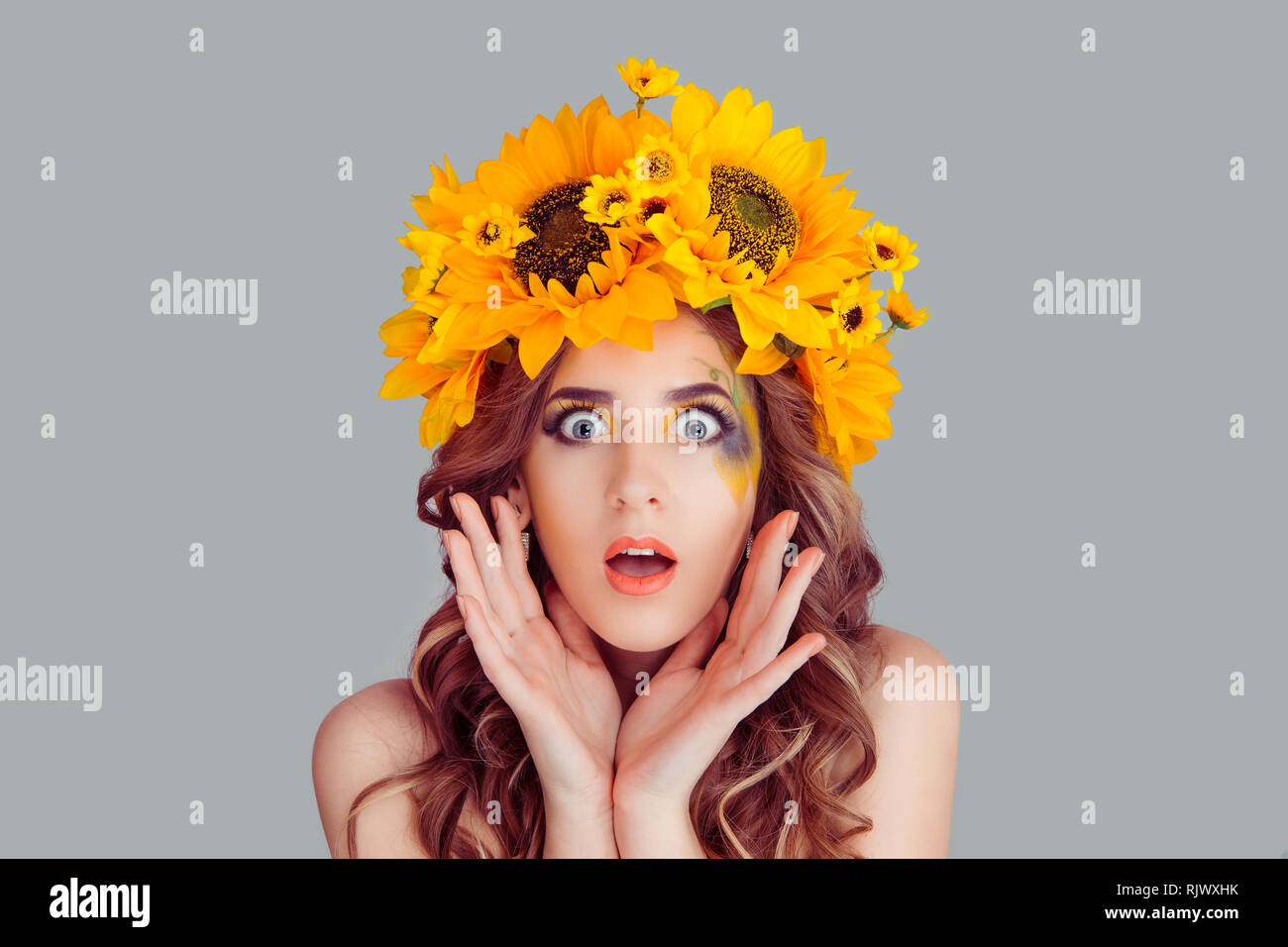 Amazed stunned Woman with floral headband looking at camera in shock. Fashion girl with crown from sunflowers on head hands near face stresses and  sh - Stock Image