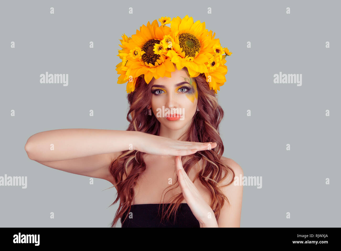 woman in crown from sunflowers making a timeout gesture - Stock Image