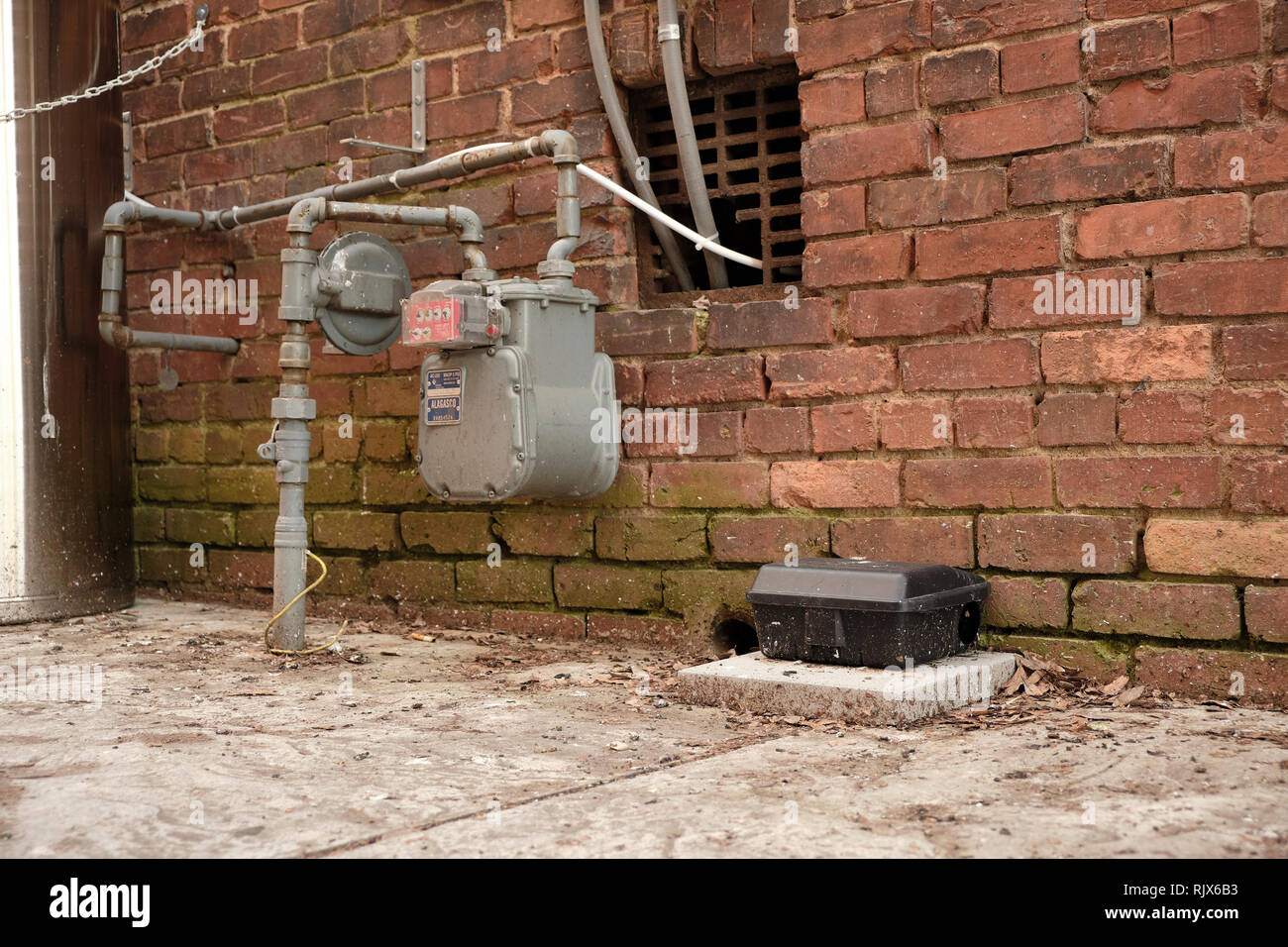 Large black rat trap box or mouse trap box next to a gas meter in a city or urban alley way in Montgomery Alabama, USA. - Stock Image
