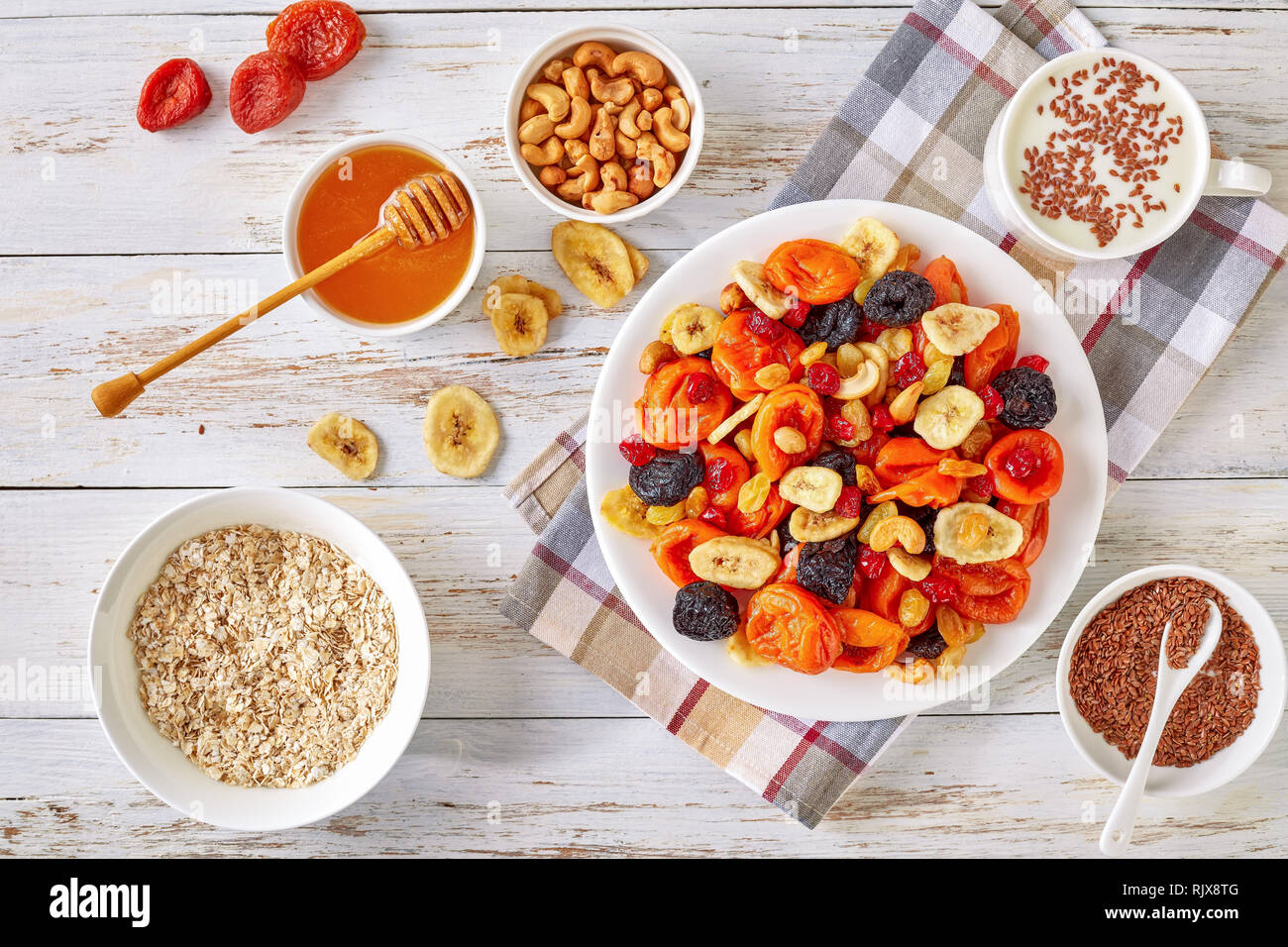 dried Fruits and Nut Mix bowl - banana slices, apricots, raisins, prunes, cherries and cashew on a rustic table with porridge, honey in a bowl and yog - Stock Image