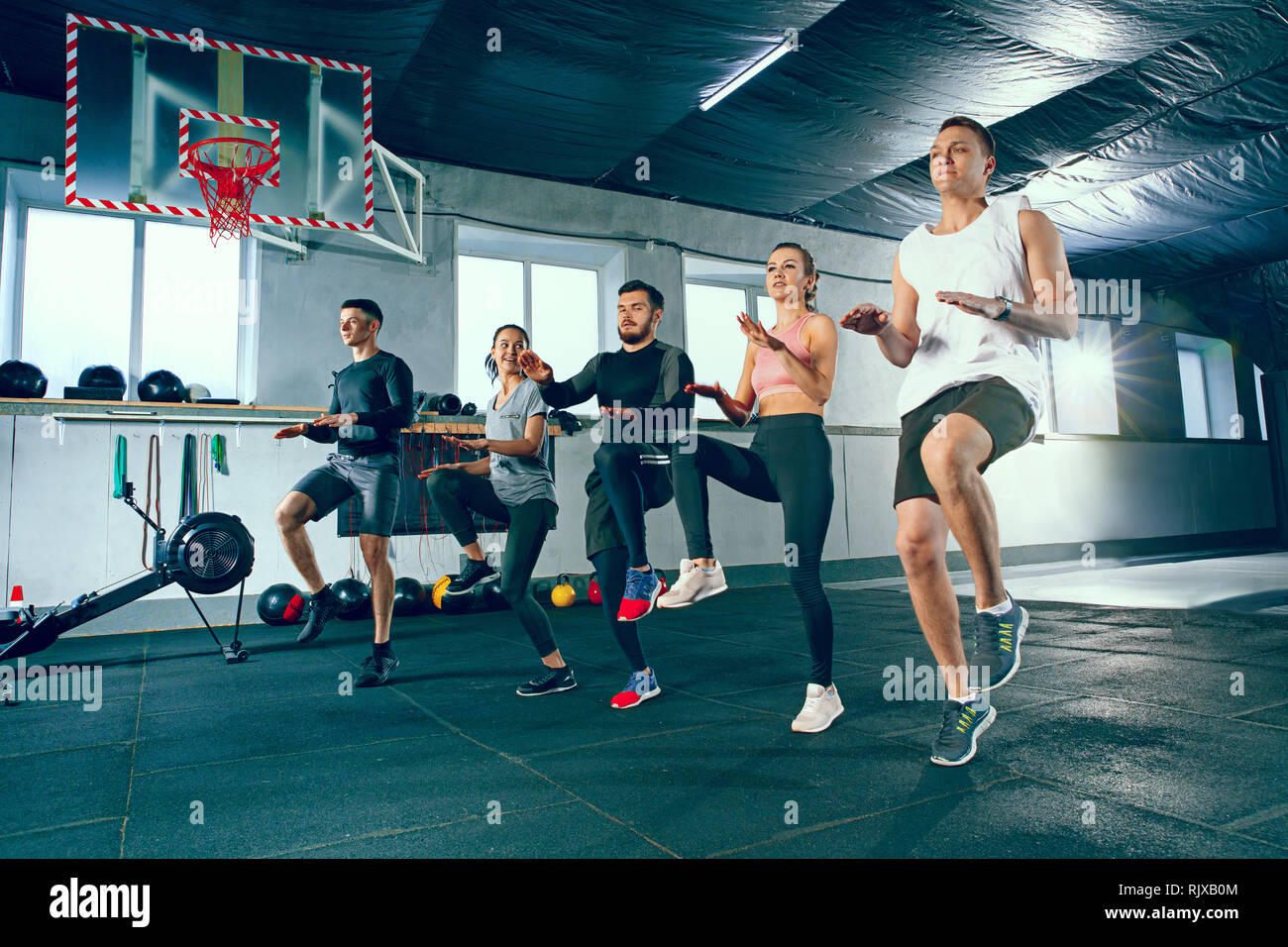 Shot of young men and women at the gym. Functional fitness workout. The group of people during training session. Fit athletic models. Healthy lifestyl - Stock Image