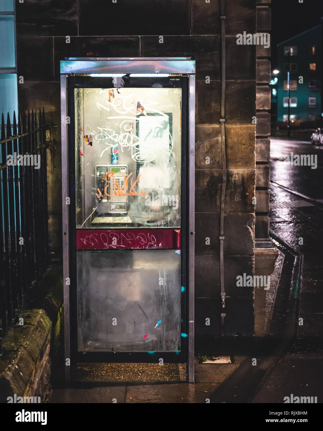 An old run down vandalised public telephone box lit up in the night on the corner of the street in Edinburgh, Scotland - Stock Image
