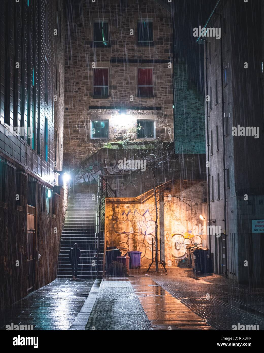A singular figure about to climb some stairs down an alleyway in the city centre of Edinburgh, Scotland during the dark evening. The wet weather pours - Stock Image