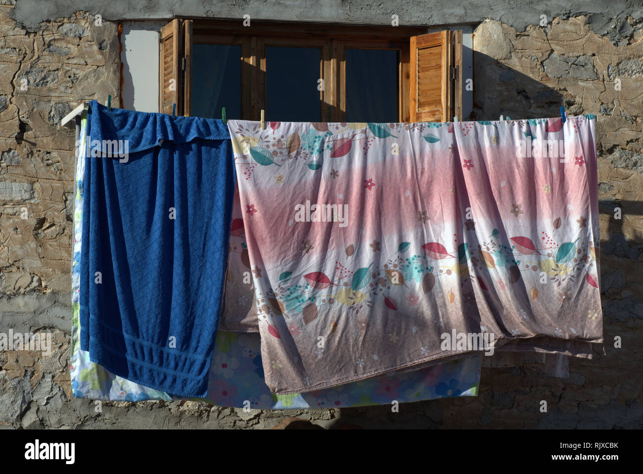 Washing hanging out to dry outside a wooden in window in the city of Kastoria, Greece. - Stock Image