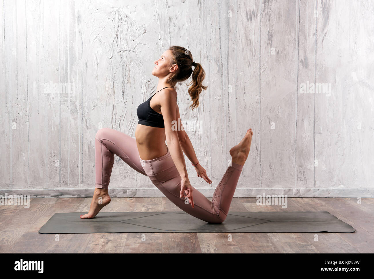 Anjaneyasana yoga pose shown by young woman in training pants and top, exercising indoors against grey wall and viewed from her side - Stock Image