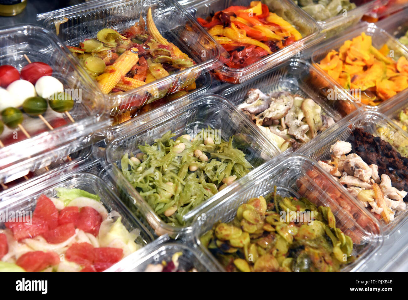 Ready to eat prepared food displayed in metal bins at a shop, restaurant or delicatessen for a buffet style meal - Stock Image