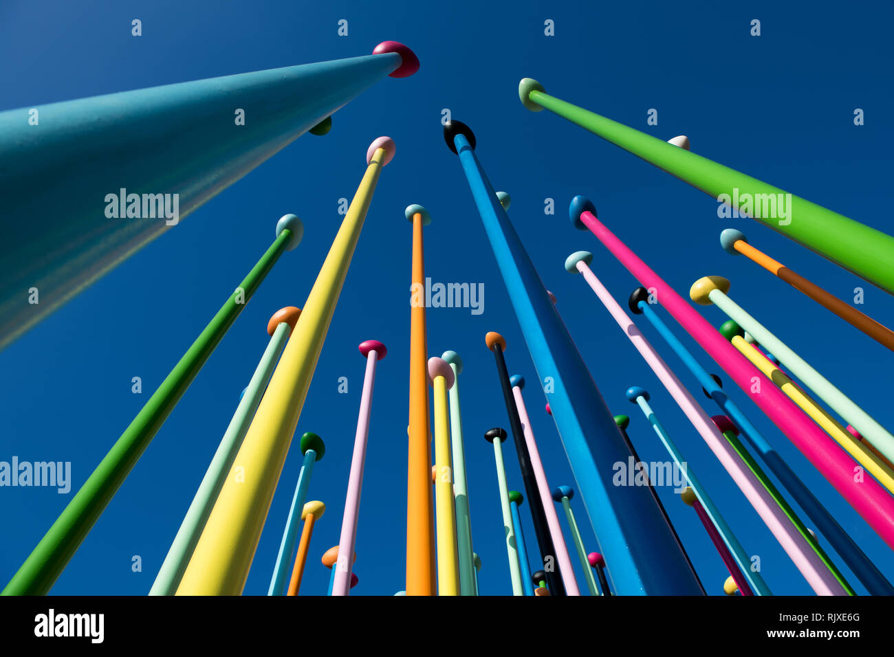 Low angle of colorful thin poles against blue sky. Art installation. Positive and bright background concept - Stock Image