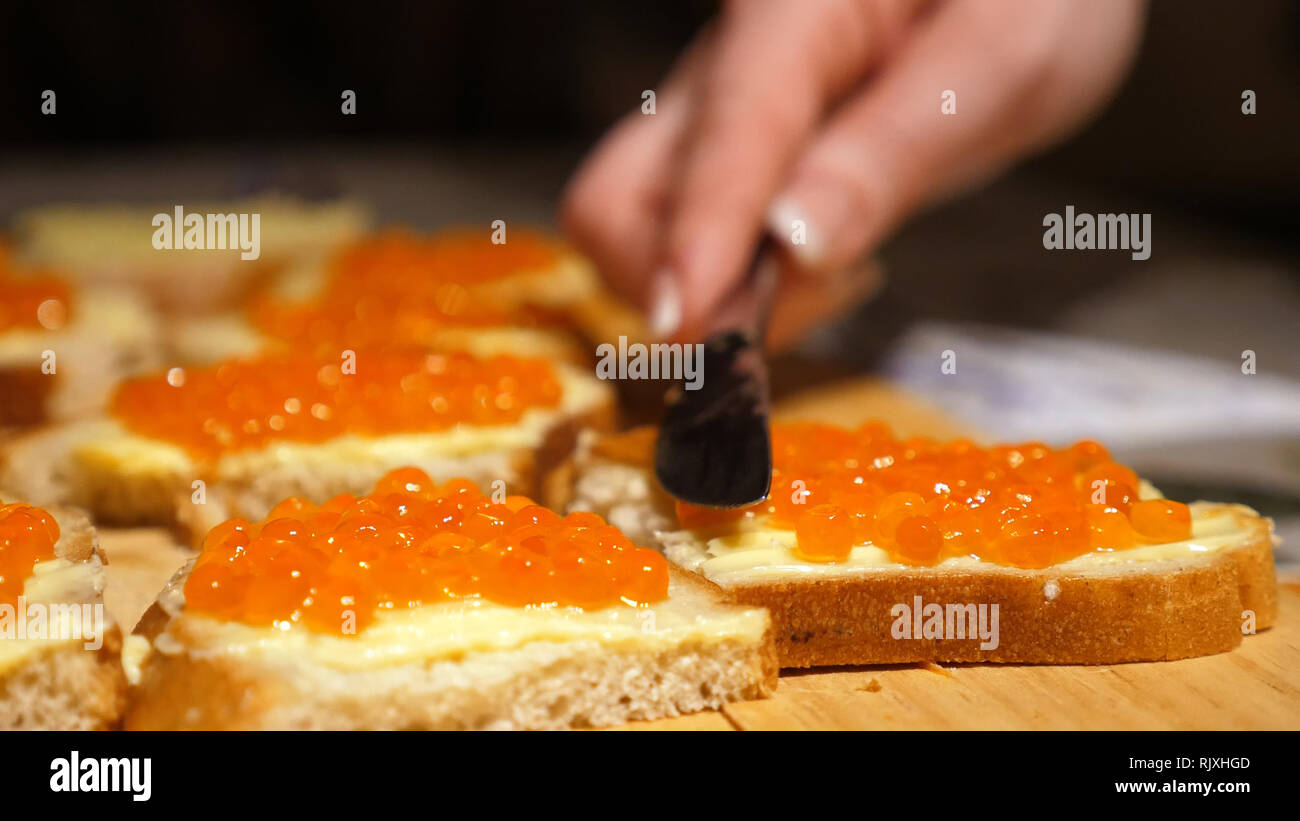 female hands spreads red caviar with knife on bread with butter for party snacks - Stock Image