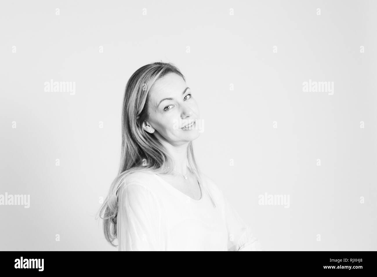 Portrait of beautiful woman in a white dress against white background Stock Photo