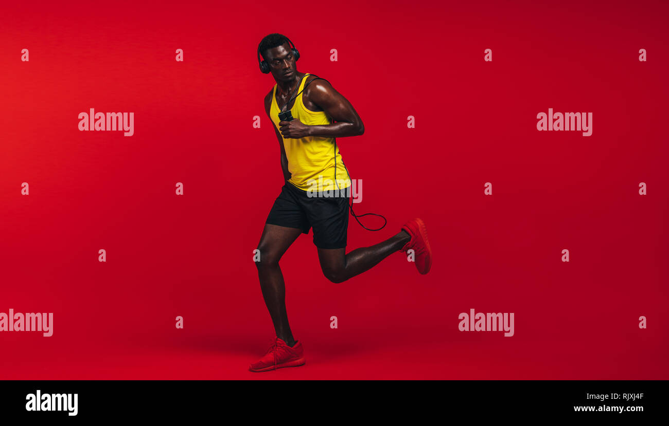 Full length of healthy young african man running with jumping rope over red background. African fitness model in sports wear working out in studio. - Stock Image