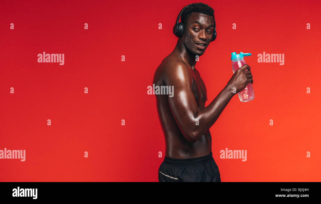 African american man with muscular body looking away while drinking water from a bottle on red background. Fit man listening music with headphones dur - Stock Image