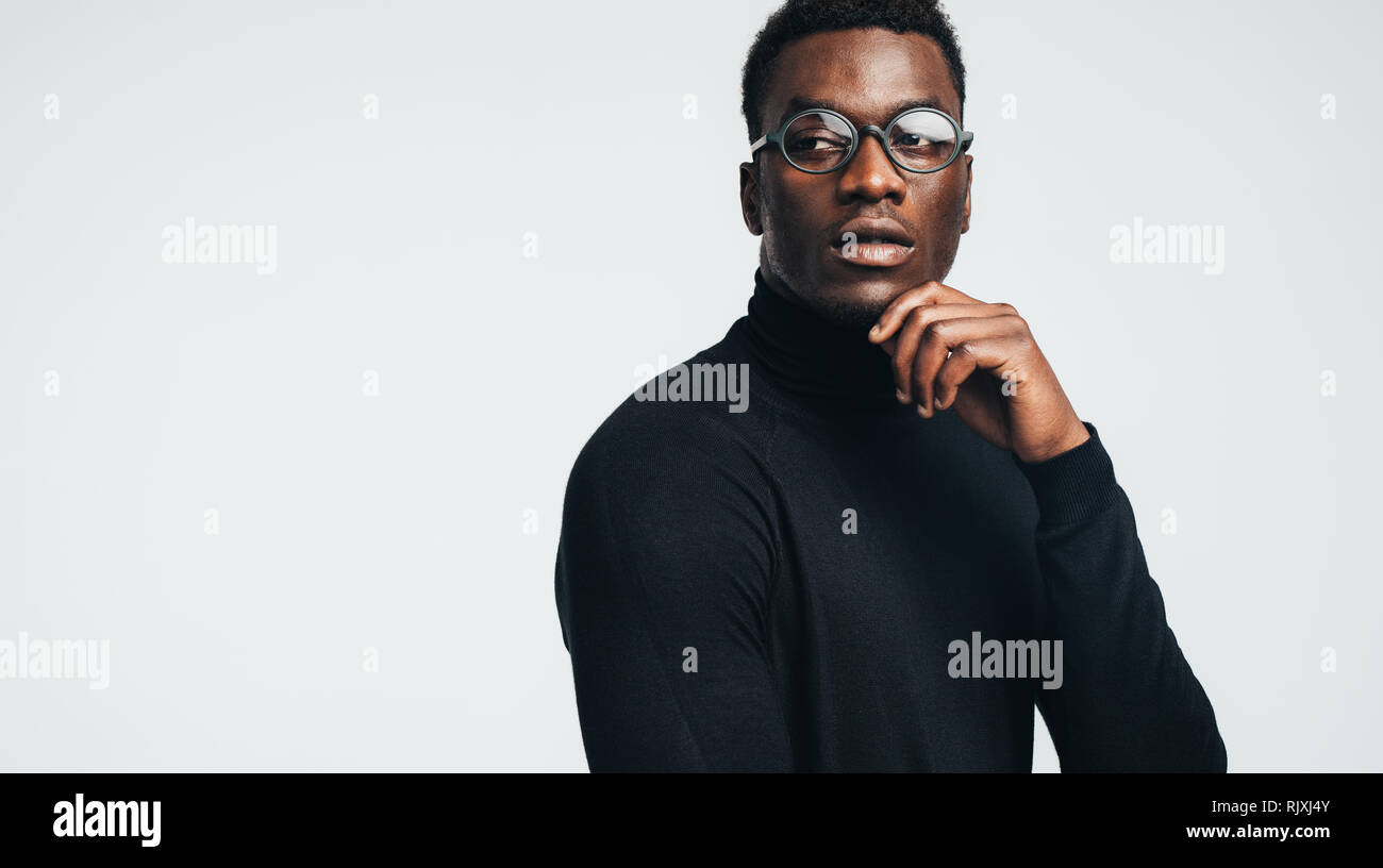 06e50a46f8ab Handsome young african man in black polo t-shirt and eyeglasses looking  away against gray