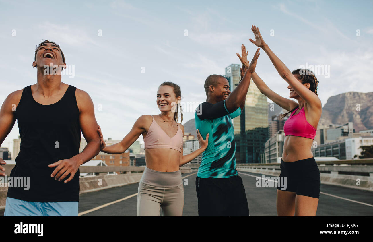 Fit young men and women exercising outdoors. Group of young people giving high five and enjoying after a sprint in the city. - Stock Image