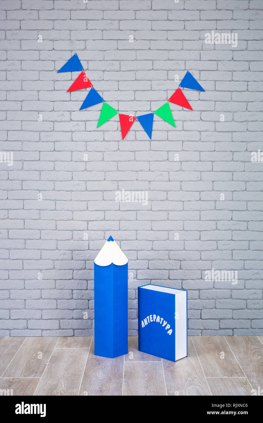 Studio shoot of school book pencil colorful flags on grey brick wall. School study decorations.On blue book written on russian - Literature - Stock Image