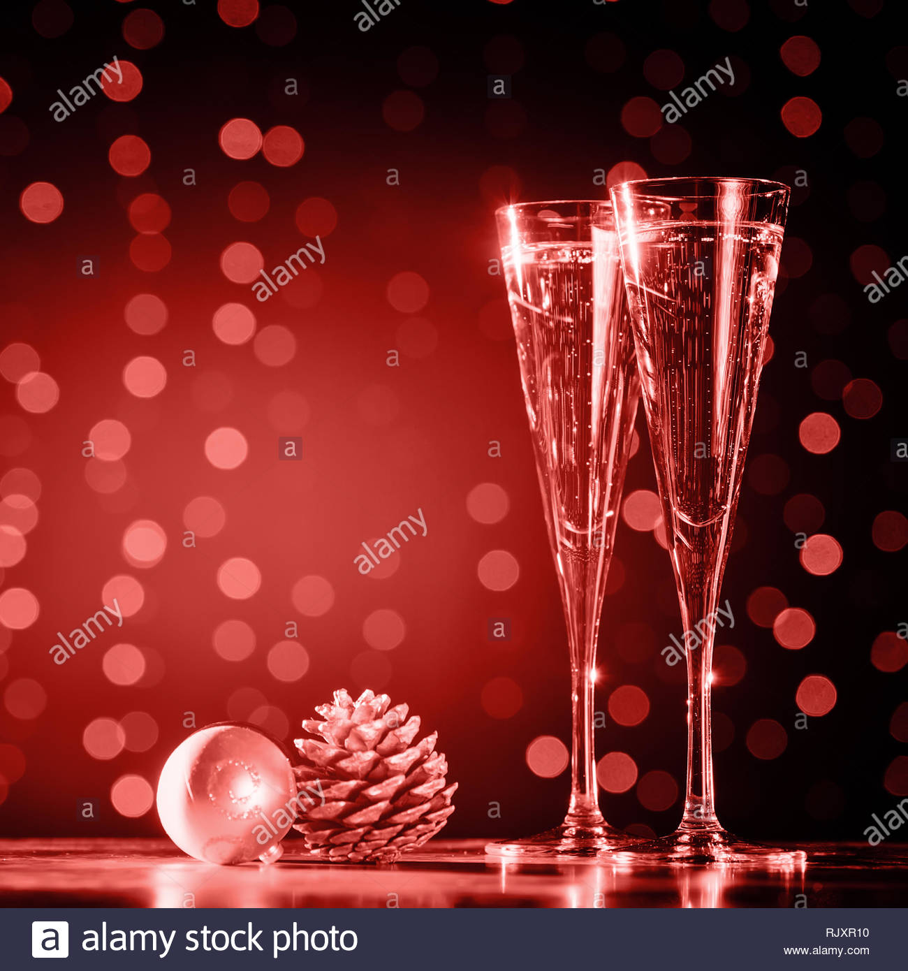 Two glasses of champagne with Christmas toys. Festive lights bokeh Christmas background. New Year holidays celebration. Square, warm tone. Living cora - Stock Image