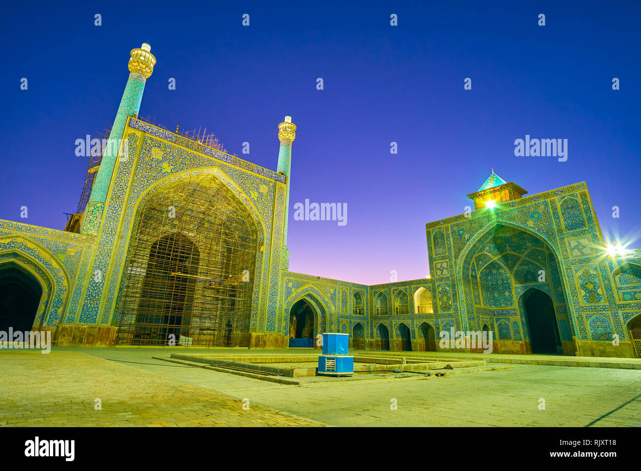 The tile decorated portals of Shah Mosque with authentic persian double minaret and a small goldast on the top of the right iwan, Isfahan, Iran - Stock Image