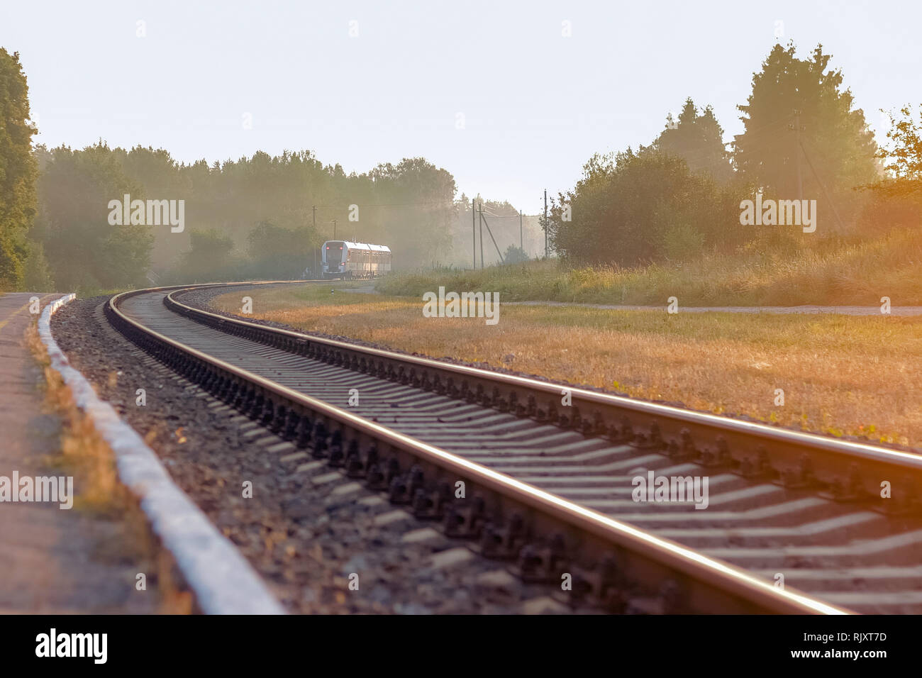Train leaving on railroad on a beautiful foggy morning  with trees in the background and sun light on the side - Stock Image