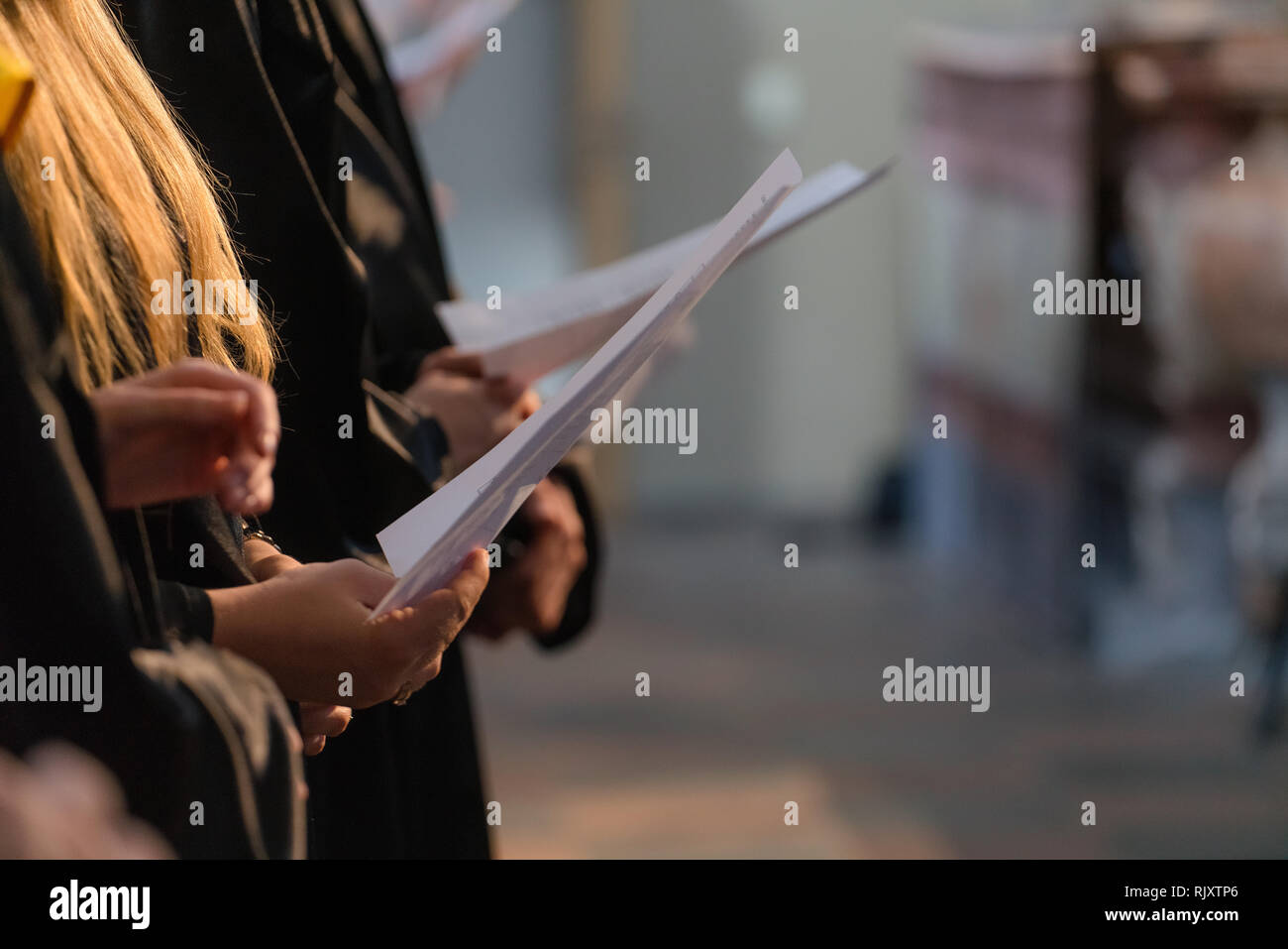 Choir singers holding musical score and singing on student graduation day in university, college diploma commencement - Stock Image