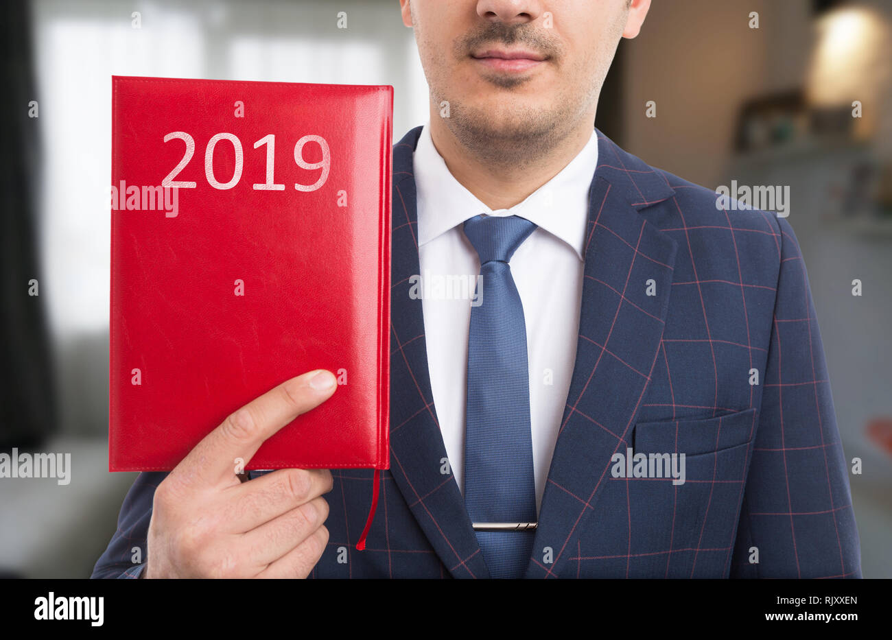 Man holding red notebook with year written on leather cover with white letters - Stock Image