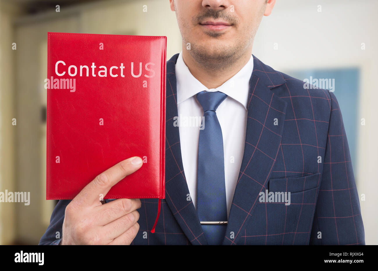 Businessman advertising communication services as holding with hand red notebook having contact us text on leather cover - Stock Image