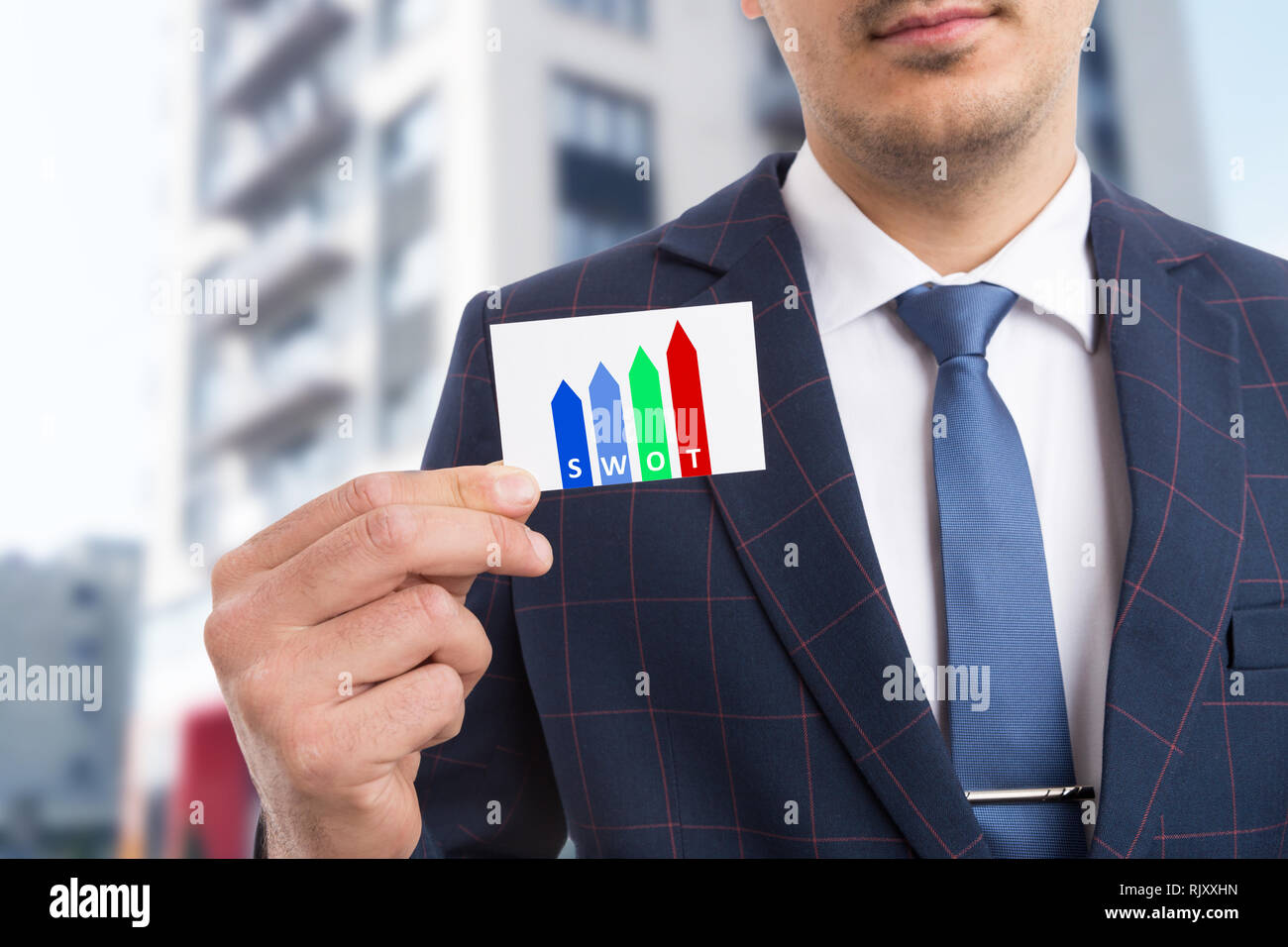 Man holding card presenting swot method as initials for strengths weaknesses opportunities threats in business strategy concept - Stock Image