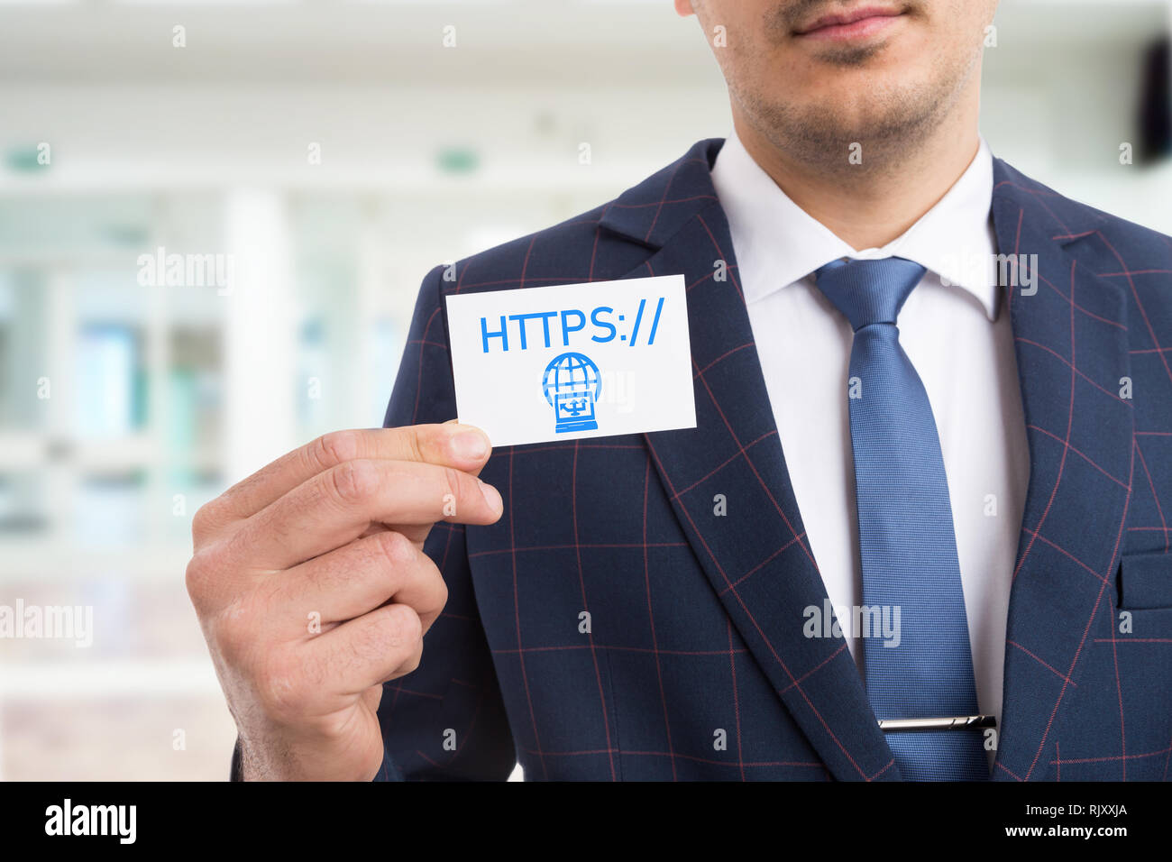 Businessman holding white card with hands as presenting website by showing https letters and computer connection symbol - Stock Image