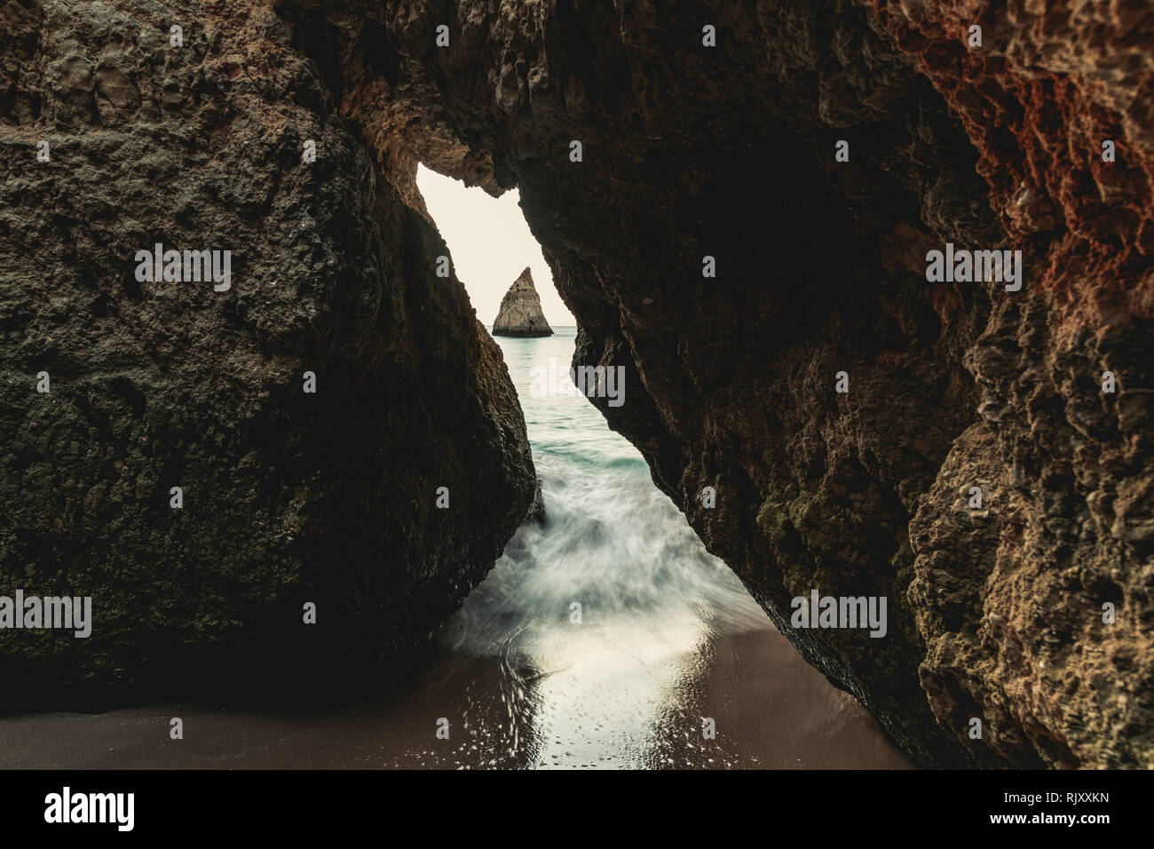 Looking through opening in cliff at pointy rock formation in distance, time lapse, Alvor, Algarve, Portugal, Europe - Stock Image