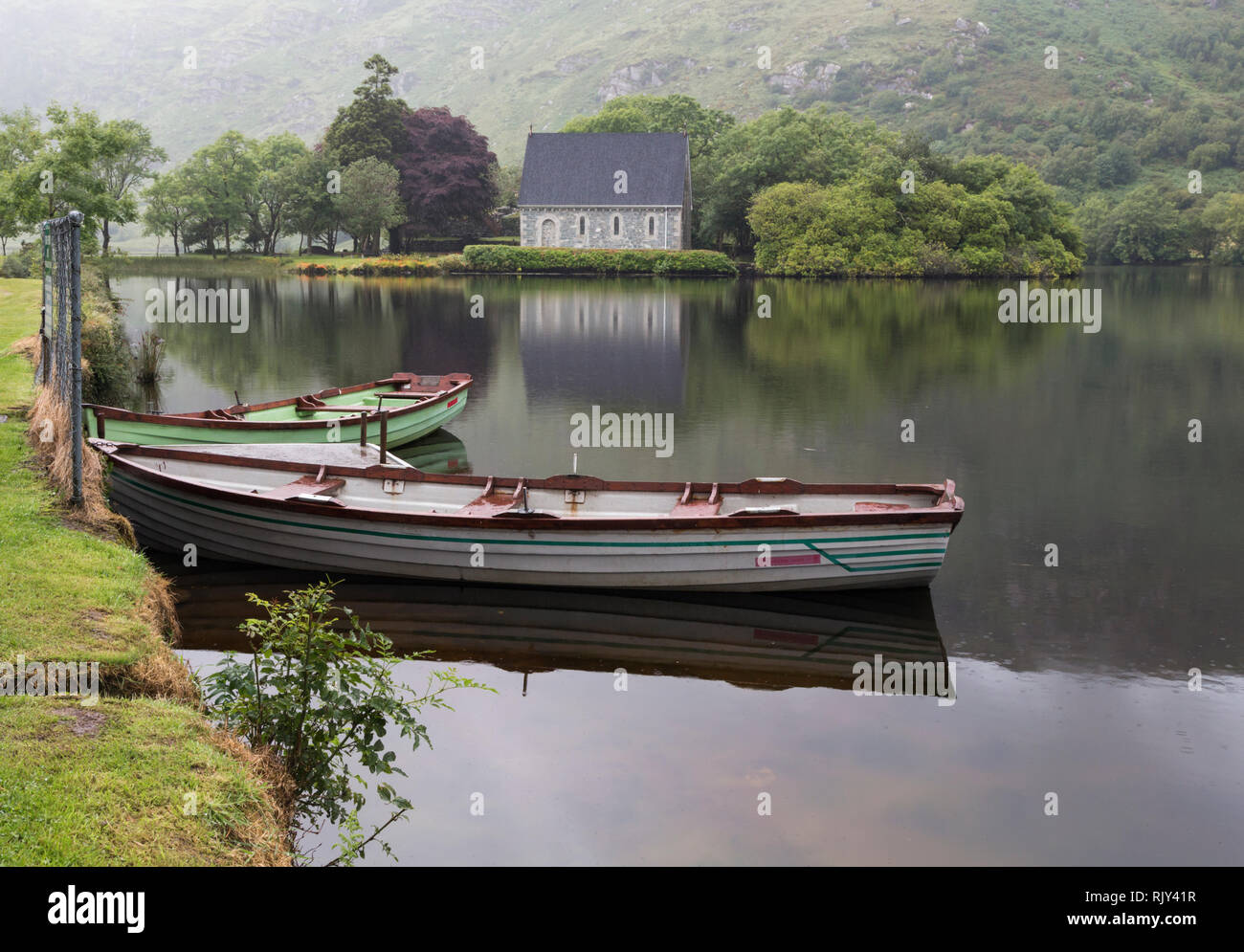 St Finbarr's Oratory seen across the lake at Gougane Barra, County Cork, Republic of Ireland.  Eire. Rowing boats in foreground. - Stock Image