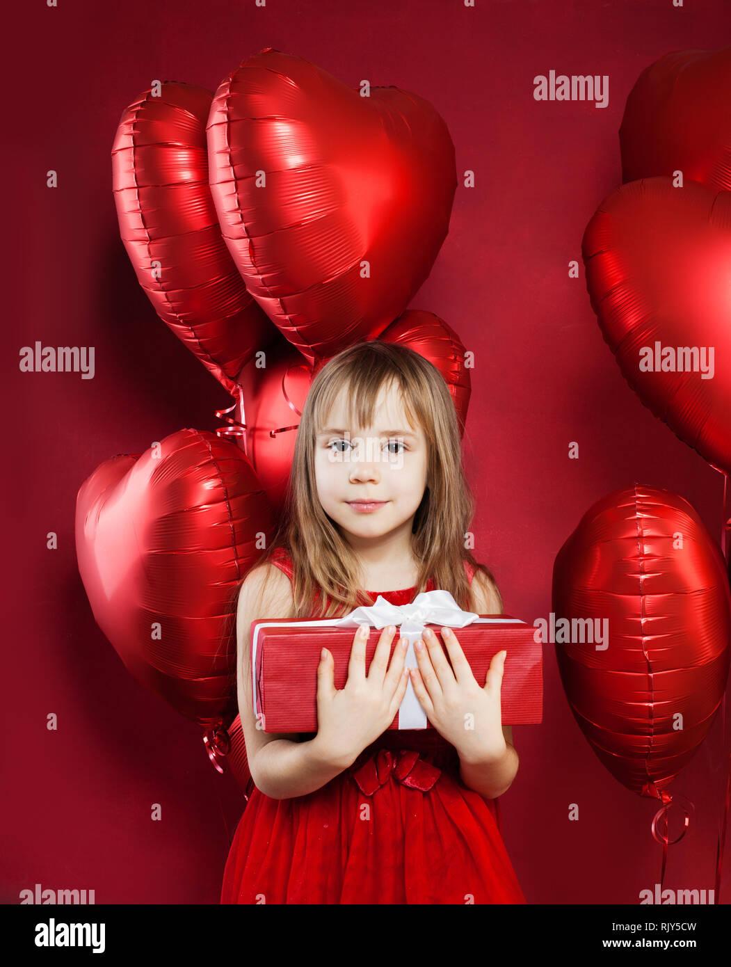 2cf32d23e130 Joyful little girl in red tulle dress holding birthday gift box on ...