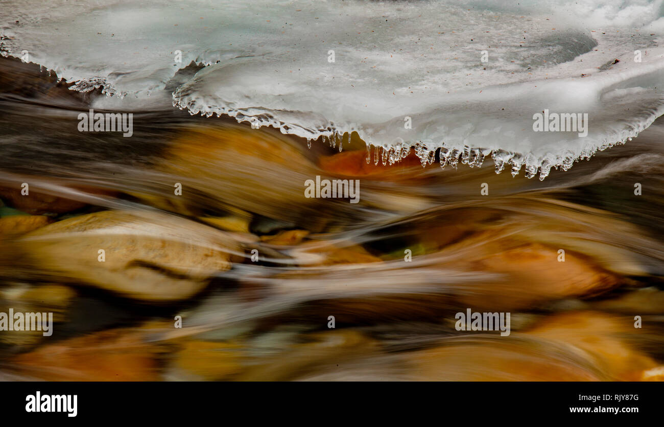 Background texture of river running swiftly under growing shelf of ice - Stock Image