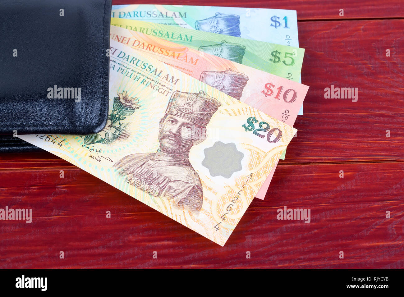 Money from Brunei in the black wallet - Stock Image