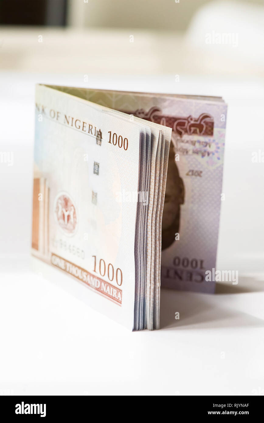 Nigerian Money - A folded wad of 1000 Naira notes on a table - Stock Image