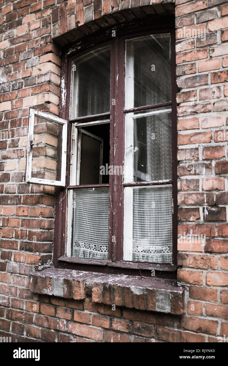 open window in rundown Eastern European brick tenement house Stock Photo