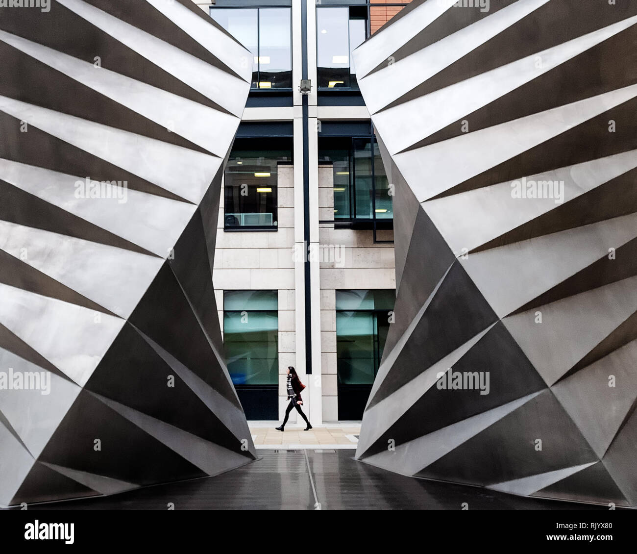 A lone figure can be seen walking past the two vents in Paternoster Square, Paternoster Row, London, EC4M England. Known as the Angel's Wings. - Stock Image