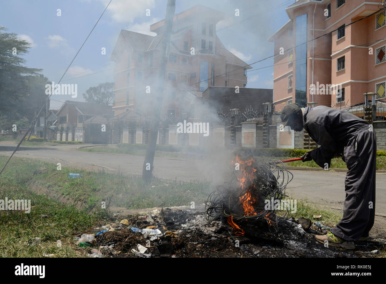 KENYA, Nairobi, city centre, waste picker burns garbage and cable insulation of electric cable on the road to collect copper - Stock Image