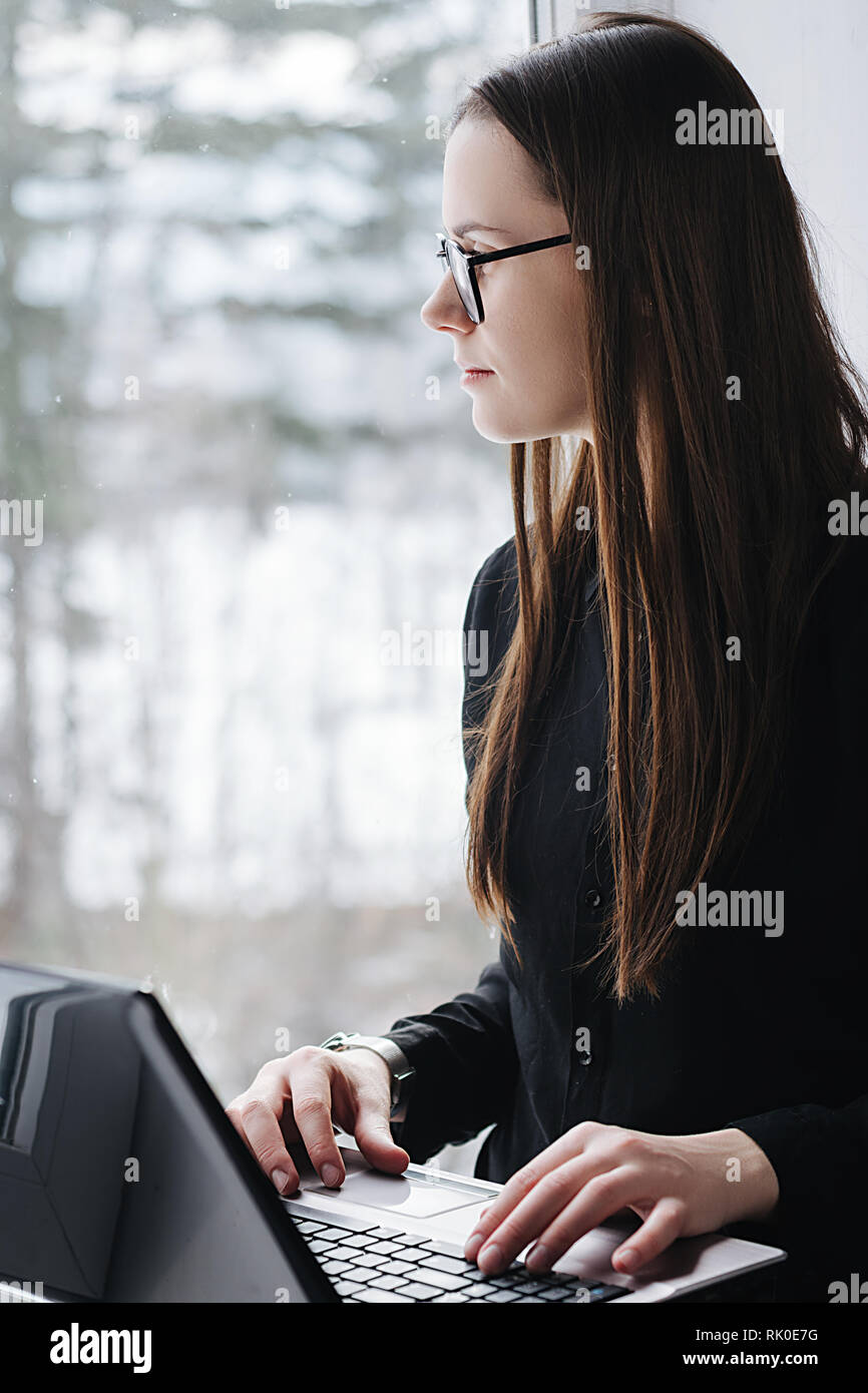 Girl in the glasses is working on a portable computer at home. Attractive young woman sits near window and typing messages on a laptop. - Stock Image